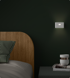 Bedside table and bed lit up by Wyze night light