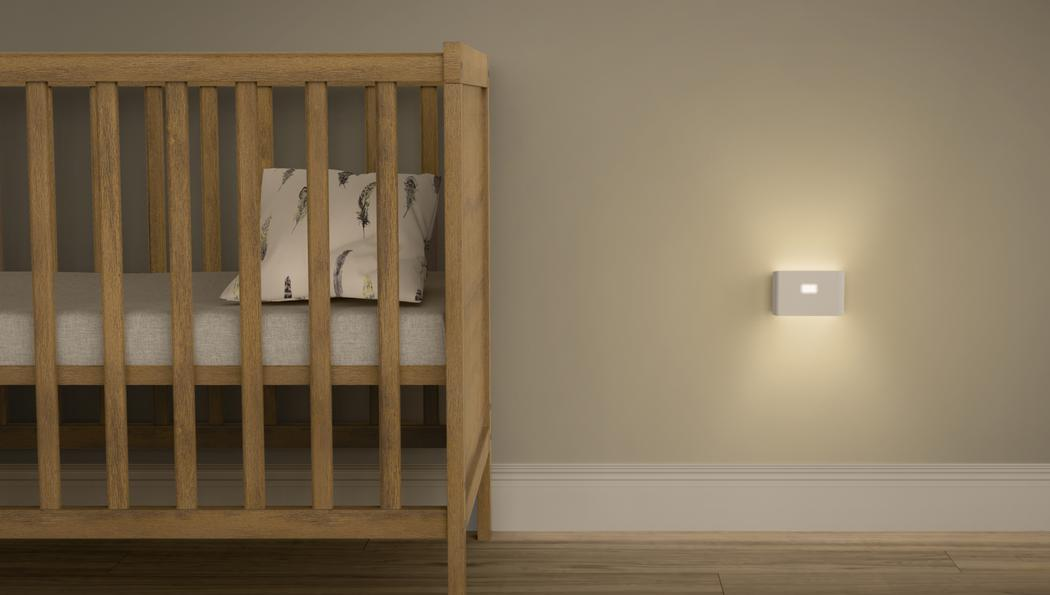 Baby crib in bedroom with Wyze night light nearby