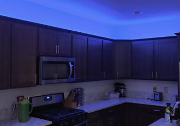 Top of kitchen cabinents illuminated by blue light from Wyze lightstrip
