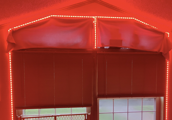 Top of living room window lit by red light from Wyze Lightstrip