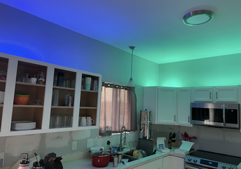 Green Wyze Lightstrip illuminating above kitchen cabinets