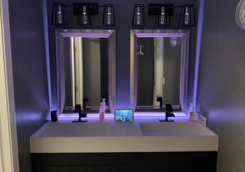 Purple Wyze Lightstrip illuminating around bathroom mirror