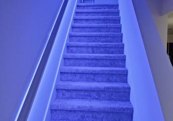 Blue Wyze Lightstrip illuminating a living room stairwell