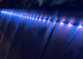 Purple Wyze Lightstrip hanging and illuminating along outdoor fence