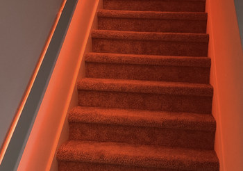 Red Wyze Lightstrip illuminating a living room stairwell