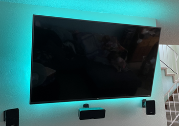 Teal Wyze Lightstrip illuminating the backside of a wall mounted tv